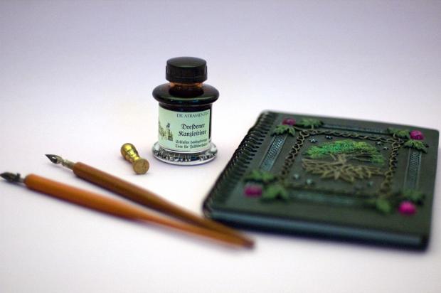 Feder - Zwei Griffel mit Stahlfedern liegen neben einem Messing-Siegel, einem Fläschchen Dresdener Kanzleitinte und einem Notizbuch mit verziertem Einband. Der Einband zeigt keltische Knoten, einen Baum und vier violette Ziersteine.