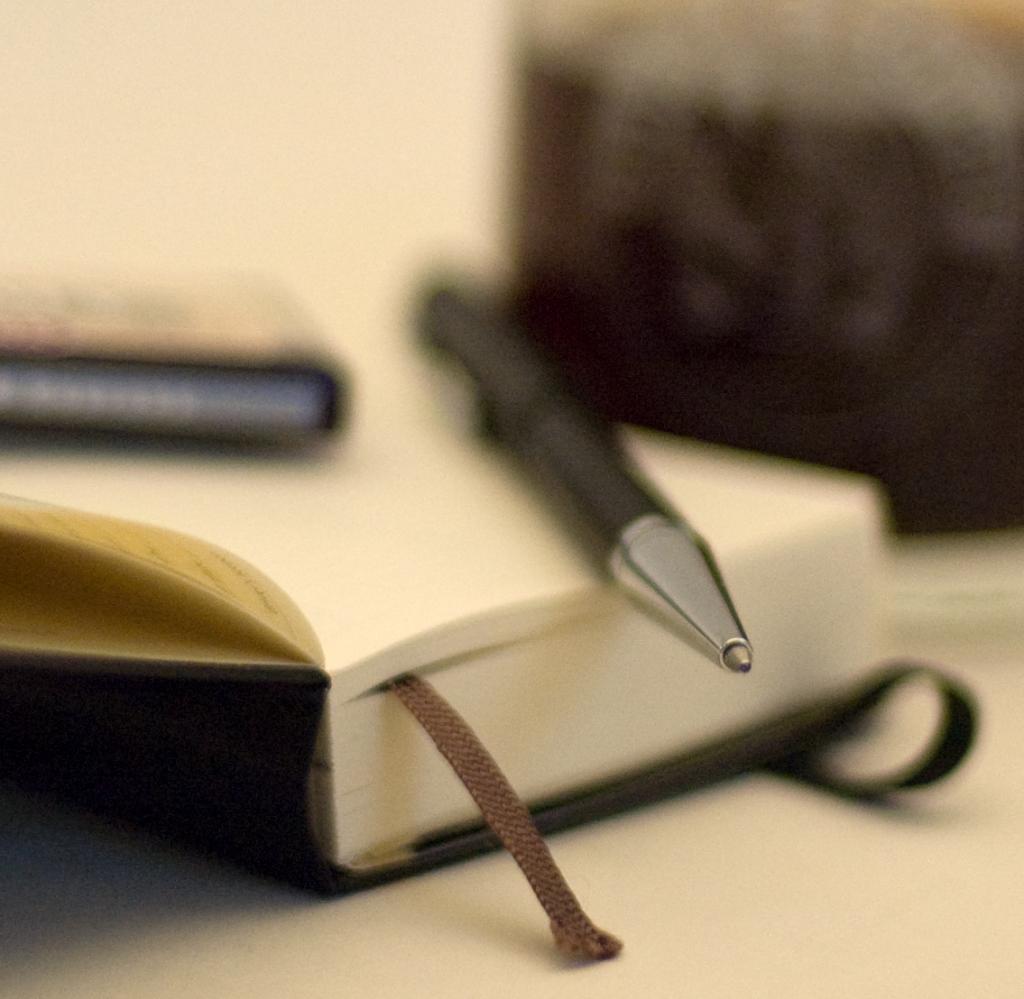 Write - Ein Kugelschreiber liegt auf einem Notizbuch, dahinter steht ein Glas Kaffee. Nur die Spitze des Kugelschreibers ist im Fokus.